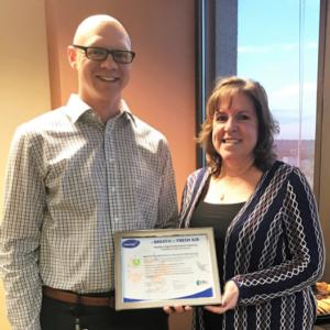 FBG Service Corp's Terri Gogetap presents the  GREENGUARD certificate to Tim Malik of First National Bank Omaha.